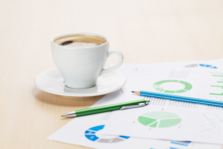 jalousie: Office workplace with coffee cup and charts on wooden desk table