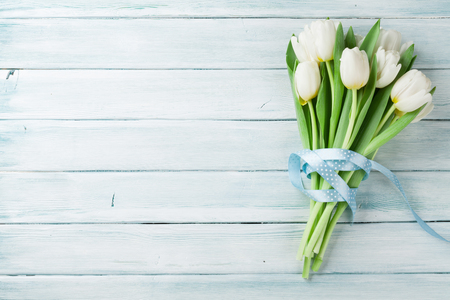 White tulips bouquet on wooden background. Top view with space for your text Foto de archivo