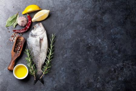 la cuisine de poisson cru et des ingrédients. Dorado, citron, herbes et épices. Vue de dessus avec copie espace sur la table en pierre