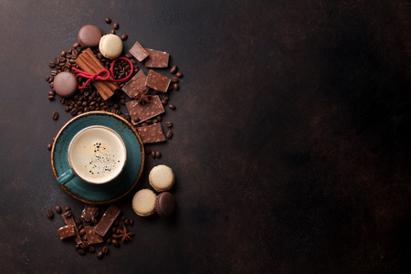 Coffee cup, beans, chocolate and macaroons on old kitchen table. Top view with copyspace for your text