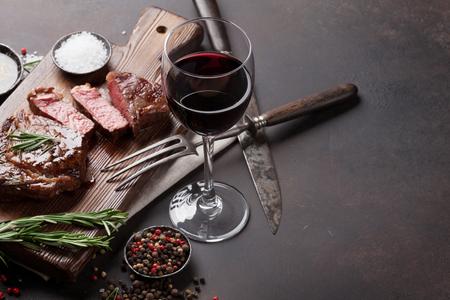 リブアイ ステーキの赤ワイン、ハーブや石のテーブルの上のスパイス焼き
