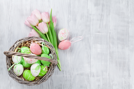 Easter eggs basket and pink tulips bouquet on wooden table. With space for your greetings