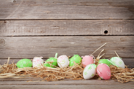 Easter eggs in front of wooden wall. With space for your greetings