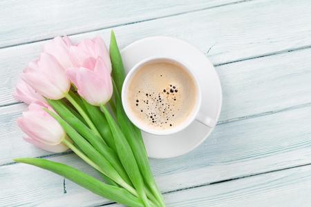 Roze tulpen en kopje koffie op houten tafel. Bovenaanzicht met een kopie ruimte