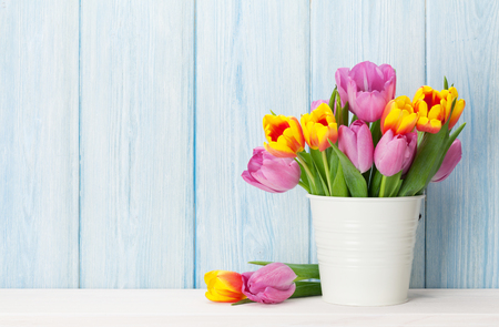 Fresh colorful tulip flowers bouquet on shelf in front of wooden wall. View with copy space Imagens - 72963381