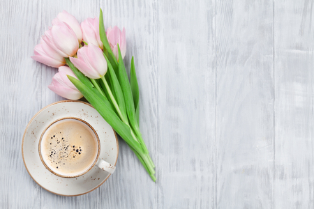 Pink tulips and coffee cup on wooden table. Top view with copy space