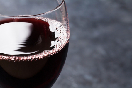 Red wine glass on stone background with copy space