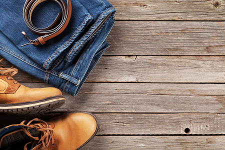 Men's clothes and accessories. Jeans, shoes and belt on wooden background. Top view with copy space Stock Photo - 72969024
