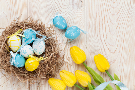 Easter background with eggs in nest and yellow tulips over white wooden table. Top view