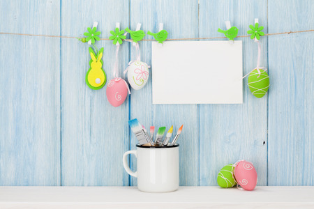 Colorful easter eggs, greeting card and paintbrushes in front of wooden wall