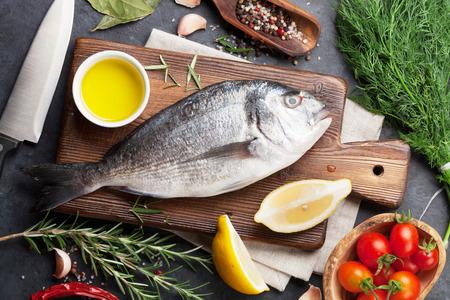 生の魚料理や食材。ドラド、レモン、ハーブおよびスパイス。石のテーブルのトップ ビュー