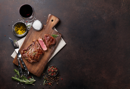 Grilled ribeye beef steak with red wine, herbs and spices. Top view with copy space for your text Stock Photo