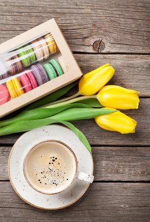 Kleurrijke macaroonkoekjes, koffiekopje en geel tulpenboeket op houten tafel. Bovenaanzicht