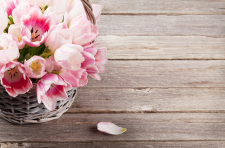Pink tulips bouquet basket on wooden table. With space for your greetings Stock Photo