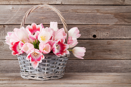 wooden basket: Pink tulips bouquet basket in front of wooden wall. Easter greeting card. With space for your greetings Stock Photo