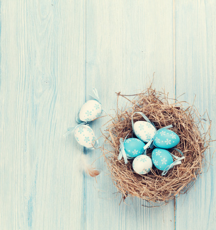 Easter eggs in nest over wooden background. View with copy space. Retro toned