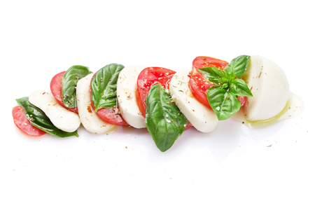 basil herb: Caprese salad. Mozzarella cheese, tomatoes and basil herb leaves. Isolated on white background Stock Photo