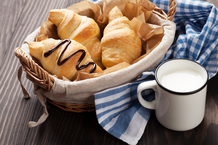 Fresh croissants basket and milk on wooden table