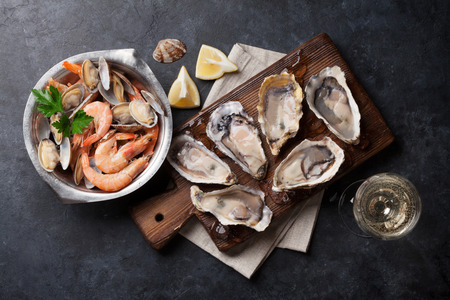 Fresh seafood and white wine on stone table. Oysters, prawns and shells. Top view
