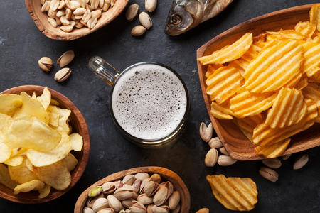 Lager beer mug and snacks on stone table. Nuts, chips, dry fish. Top view