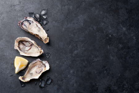 Opened oysters, ice and lemon on stone table. Top view with copy space