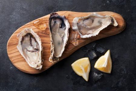 Opened oysters, ice and lemon on board over stone table. Top view