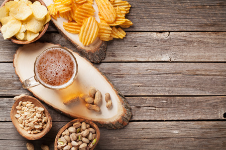 Lager beer mug and snacks on wooden table. Nuts, chips. Top view with copyspace Reklamní fotografie