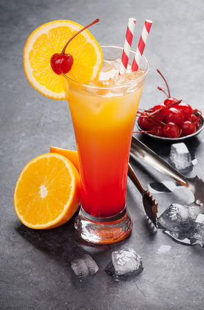 Tequila sunrise cocktail on dark stone table