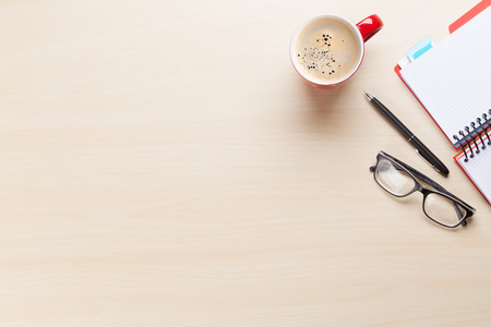 Office desk workplace with coffee cup, notepad and glasses on wooden background. Top view with copy space Stock Photo