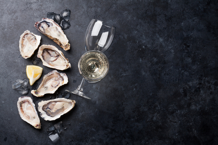 Geopende oesters, ijs en citroen met witte wijn over stenen tafel. Half dozijn. Bovenaanzicht met kopie ruimte Stockfoto