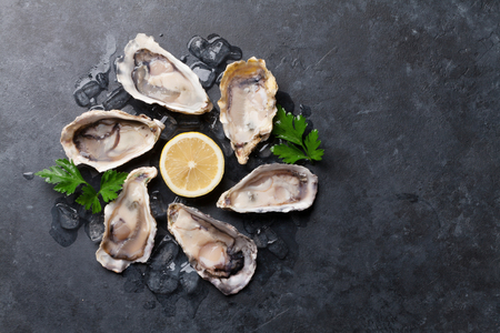 Opened oysters, ice and lemon on stone table. Half dozen. Top view with copy space Standard-Bild