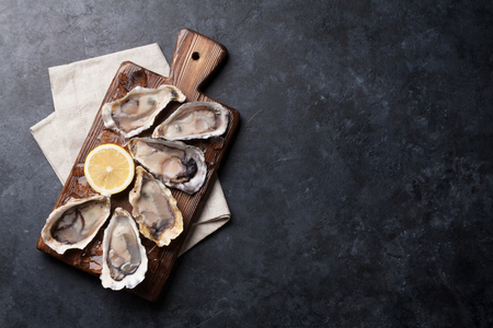Opened oysters, ice and lemon on wooden board over stone table. Half dozen. Top view with copy space