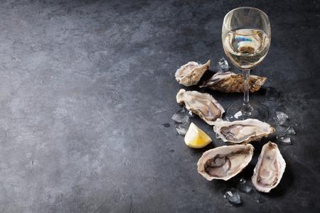 Oesters, ijs en citroen geopend met witte wijn over stenen tafel. Halve dozijn. Met kopie ruimte