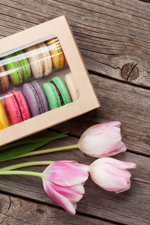 bouquet fleur: Colorful macaroon cookies and pink tulips bouquet on wooden table. Top view