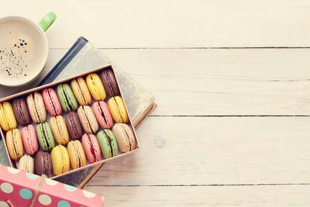 Colorful macaroons and coffee on wooden table. Sweet macarons in gift box. View with copy space for your text. Toned