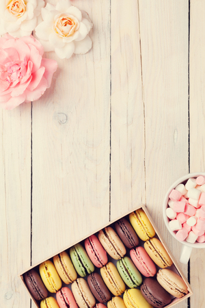 Colorful macaroons and marshmallow on wooden table. Sweet macarons in gift box. Top view with copy space for your text. Retro toned