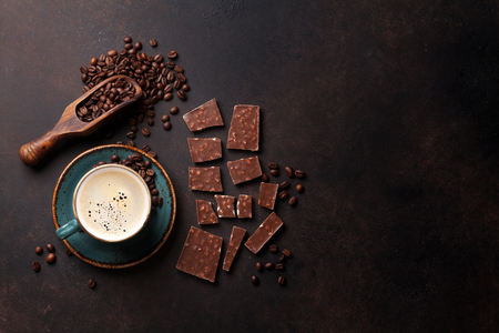 Coffee cup, beans and chocolate on old kitchen table. Top view with copyspace for your text