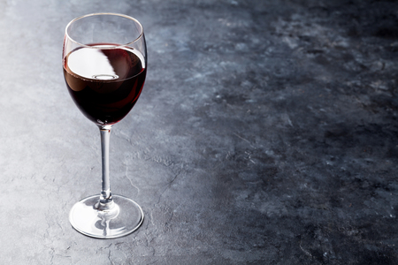Red wine glass on stone table. With copy space Stok Fotoğraf