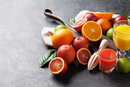 Verse citrusvruchten en sap op donkere stenen achtergrond. Sinaasappelen en limoenen. Weergave met kopie ruimte Stockfoto
