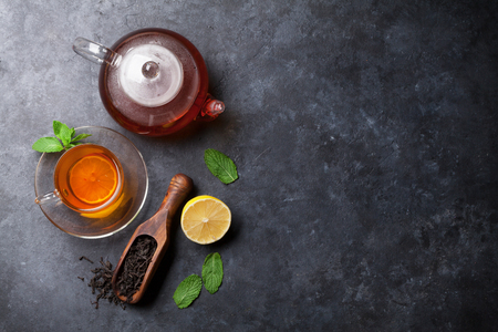 Tea cup, teapot and dry tea in spoon on stone table. Top view with copy space Stock Photo