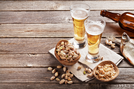 vasos de cerveza: Lager beer glasses and snacks on wooden table. Nuts and dry fish. With copy space Foto de archivo
