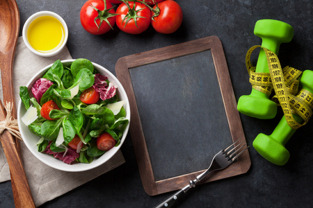 Healthy salad and fitness equipment on stone table. Top view with chalkboard for your text Stock Photo