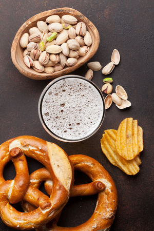 Lager beer and snacks on stone table. Nuts, chips, pretzel. Top view