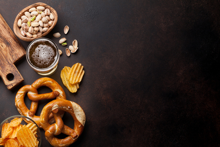 Lager beer mug and snacks on stone table. Nuts, chips, pretzel. Top view with copy space