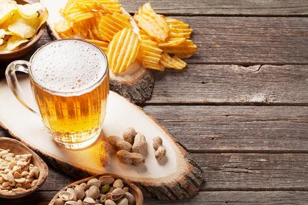 Lager beer mug and snacks on wooden table. Nuts, chips. With copy space Stock Photo
