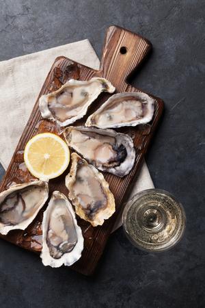 Geopende oesters, ijs en citroen aan boord en witte wijn op stenen tafel. Bovenaanzicht