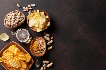 ラガー ビールと石のテーブルで軽食。ナット、チップ。Copyspace のトップ ビュー 写真素材