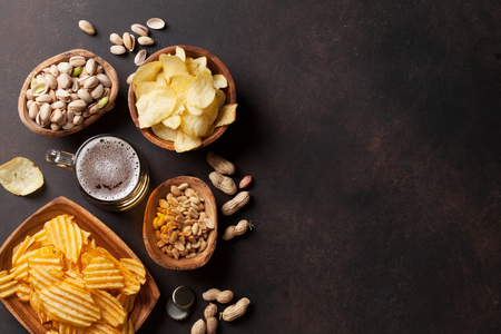 Lager beer and snacks on stone table. Nuts, chips. Top view with copyspace Foto de archivo