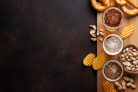 Lager beer and snacks on stone table. Nuts, chips, pretzel. Top view with copy space