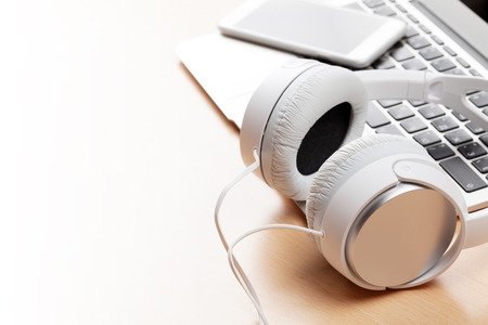 Headphones over laptop on wooden desk table. Music concept. View with copy space Stock Photo